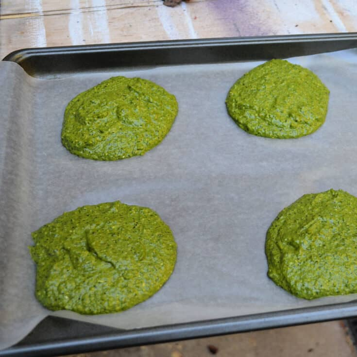 4 patties of Homemade basil pesto on a parchment covered cookie sheet