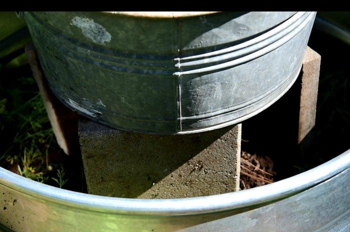 galvanized tub balanced on concrete pavers, DIY planter with solar fountain