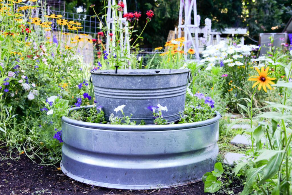 galvanized fire ring with tub fountain in center of garden